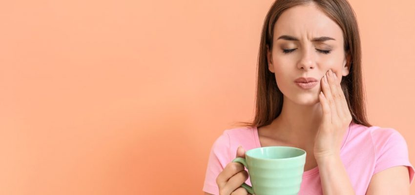 Une femme souffre de sensibilité dentaire